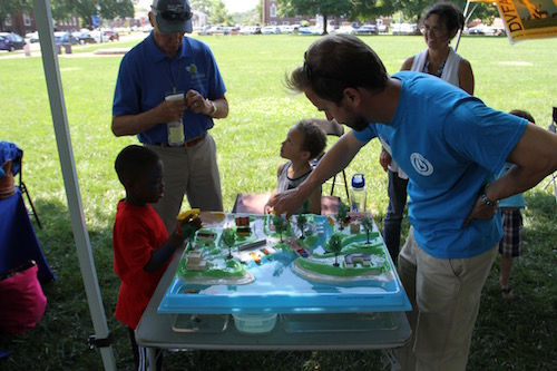 Roy Miller CIB Policy Coordinator and CIB Executive Director Chris Bason help two kids use the enviroscape which shows how water works through an ecosystem