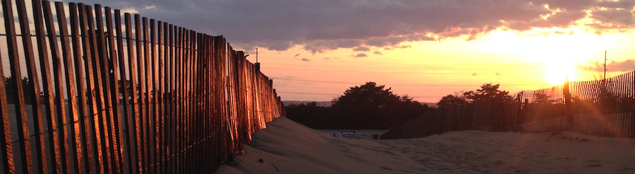 sunet behind beach dune with fence